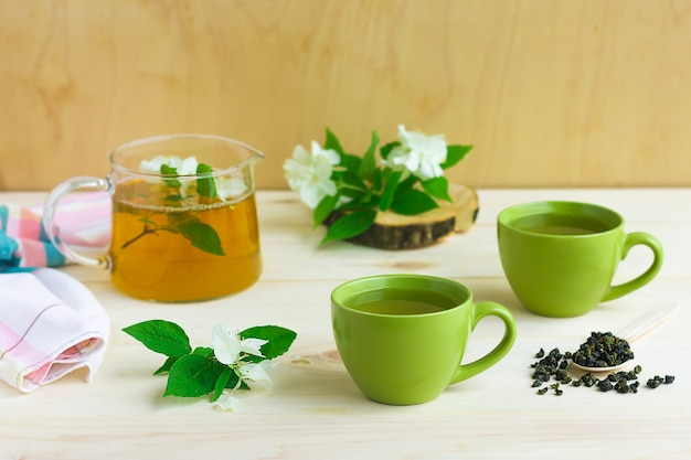 Композиция с двумя чашками зеленого травяного чая с цветком жасмина и чайником
