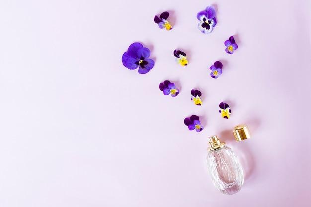 Композиция, украшенная свежими красивыми яркими цветами, ароматная и аэрозольная бутылка с женскими духами. фиалки. вид сверху.