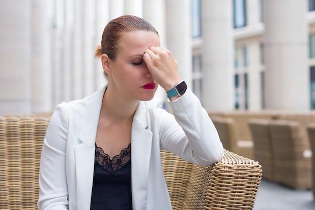 疲れたストレスの多い実業家やオフィスワーカー、従業員はカフェの椅子に座って、手で彼女の頭を保持しています。頭痛、片頭痛に苦しんでいる少女