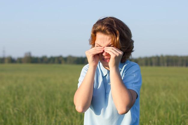 かゆみに苦しんでいる若い女性は、夏の公園で屋外で目をこすり、うんざりした女性が目をこすります。目は疲れて、水っぽい。女性は泣いています。