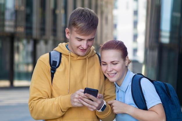 美しい幸せなカップル、携帯電話、携帯電話、笑顔、見て楽しんでいるバックパックを持つ学生。