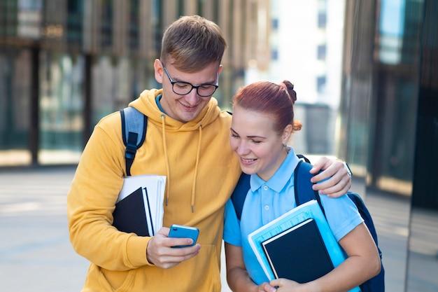 美しい若いカップル、バックパック、本、キャンパスで一緒に屋外で立っている教科書を持つ幸せな学生。