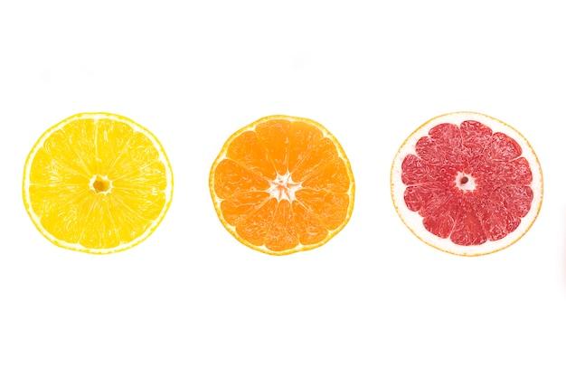 Кусочки цитрусовых: желтый сочный лимон, спелый апельсин, красный свежий грейпфрут.