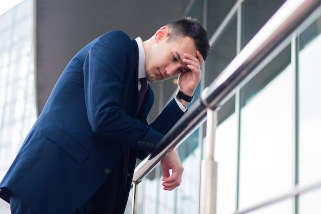 疲れて動揺して実業家は手すりに傾いています。