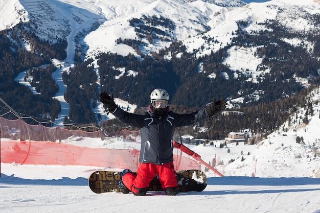 イタリアのアルプスのスキーリゾートでリラックスした瞬間に座っているスノーボーダー-山に登る準備ができている人との冬のスポーツコンセプト
