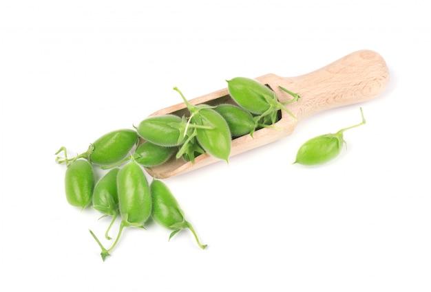 ホワイトスペースに分離された緑豆ひよこ豆。木のスプーンに緑のひよこ豆