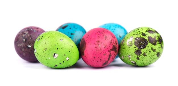 Пестротканые пасхальные яйца изолированные на белом космосе. цветные перепелиные яйца