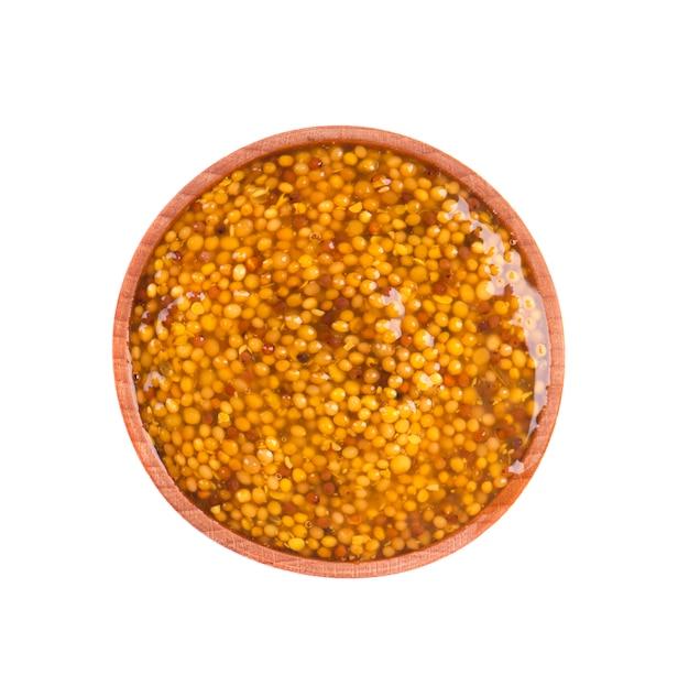 Цельнозерновая дижонская горчица в деревянной миске с коричневыми семечками. конец фото еды макроса вверх, изолированный на белом космосе.