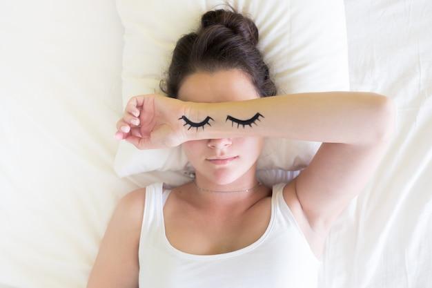 朝の時間にベッドで眠っている目とブルネットの若い女性を描いた