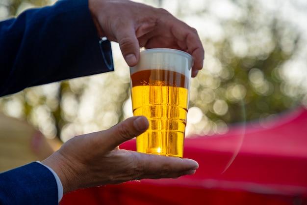 男の手がプラハの夕日の光で屋外でプラスチック製のビールのカップを保持しています。