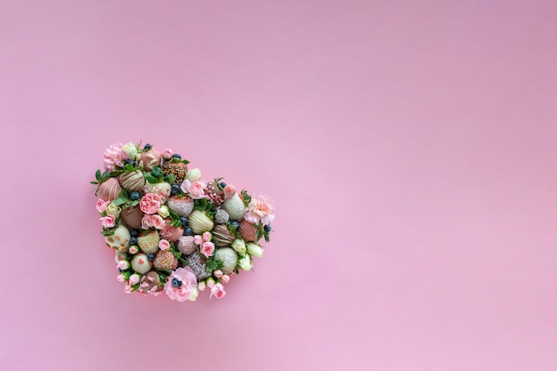 テキスト用の空き容量を持つピンクの背景にバレンタインの日にプレゼントとして手作りチョコレートで覆われたイチゴが異なるトッピングと花とイチゴのハート形ボックス