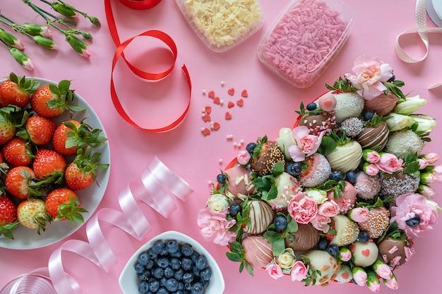 手作りのチョコレートカバーイチゴ、花、ピンクの背景にデザートを調理するための装飾