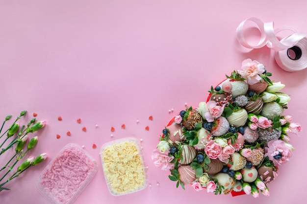 手作りのチョコレートカバーイチゴ、花、テキスト用の空き領域を持つピンクの背景にデザートを調理するための装飾