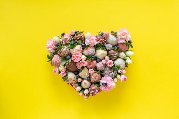 黄色の背景にバレンタインの日にプレゼントとして異なるトッピングと花と手作りのチョコレートで覆われたイチゴのハート形ボックス