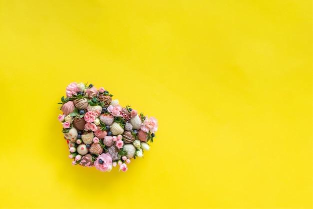 テキスト用の空き容量を持つ黄色の背景にバレンタインの日にプレゼントとして手作りチョコレートで覆われたイチゴが異なるトッピングと花でハート形ボックス