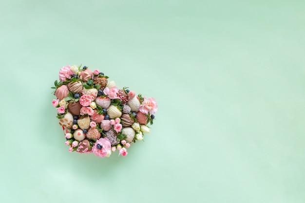 テキスト用の空き容量のある緑の背景にバレンタインの日にプレゼントとして、手作りのチョコレートで覆われたイチゴが異なるトッピングと花で飾られたハート型のボックス