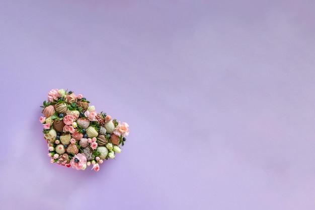 テキスト用の空き領域を持つ紫色の背景にバレンタインの日にプレゼントとして手作りトッピングと花とイチゴで覆われたイチゴのハート形ボックス
