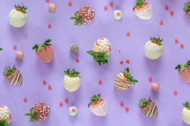 Разнообразие клубники в шоколаде с разными начинками на фиолетовом фоне