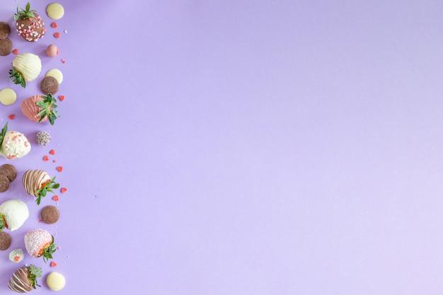 Разнообразие клубники в шоколаде ручной работы с разными начинками на фиолетовом фоне со свободным пространством для текста