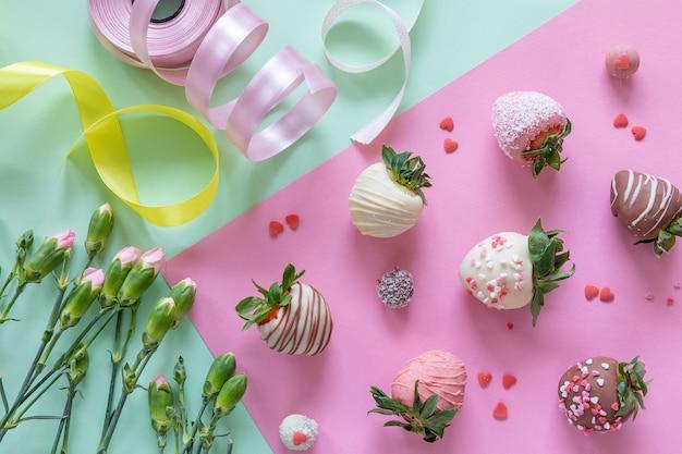手作りのチョコレートカバーイチゴ、花、色付きの背景にデザートを調理するための装飾