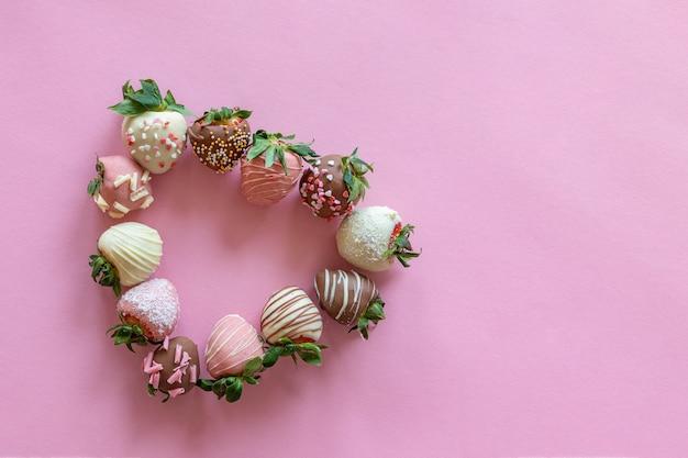 В форме сердца из клубники в шоколаде ручной работы с разными начинками на розовом фоне