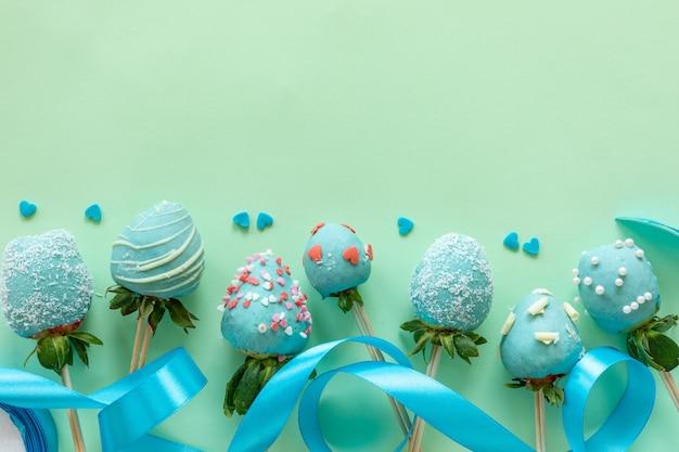 手作りのチョコレートには、イチゴ、花、テキスト用の空き容量がある緑色の背景でデザートを調理するための装飾が覆われています