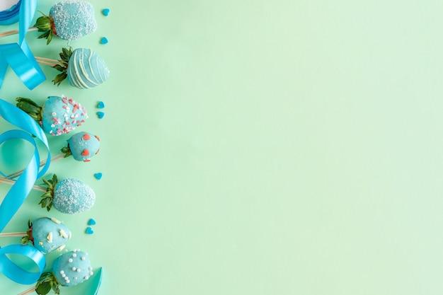 Клубника в шоколаде, цветы и украшения для приготовления десерта на зеленом фоне со свободным пространством для текста