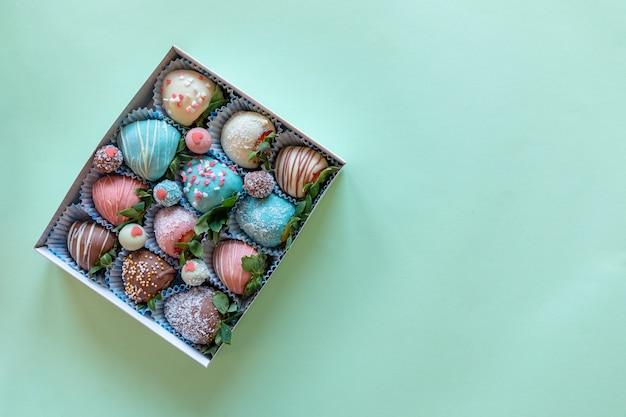 テキスト用の空き領域を持つ緑の背景にチョコレートで手作りのイチゴのギフトボックス