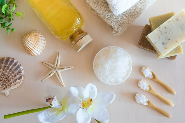 Морская соль, мыло, полотенце, оливковое масло и цветы на деревянном фоне