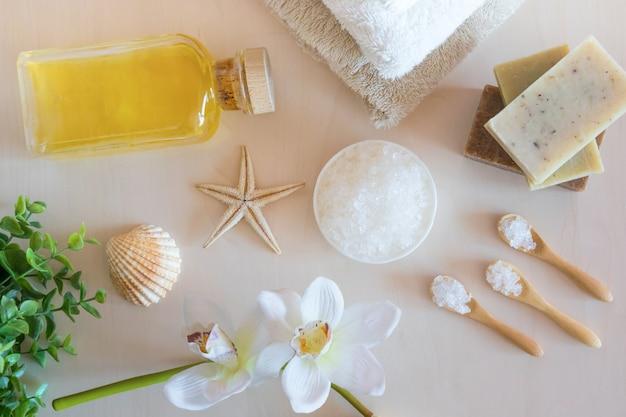 海の塩、石鹸、タオル、オリーブオイル、木製の背景の花