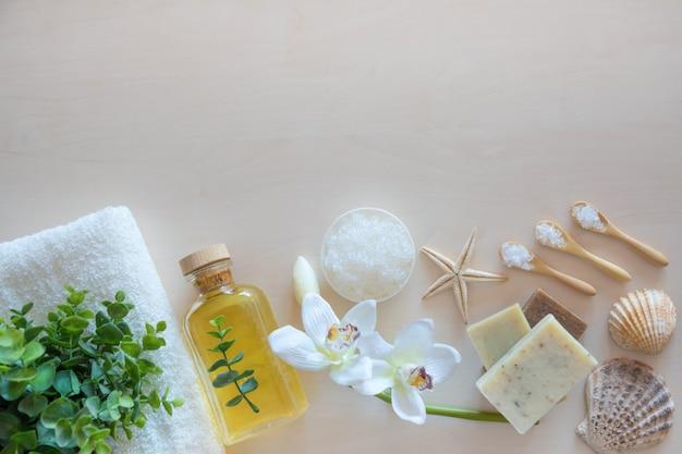 ウェルネス設定の平面図。海の塩、石鹸、タオル、オリーブオイル、木製の背景の花