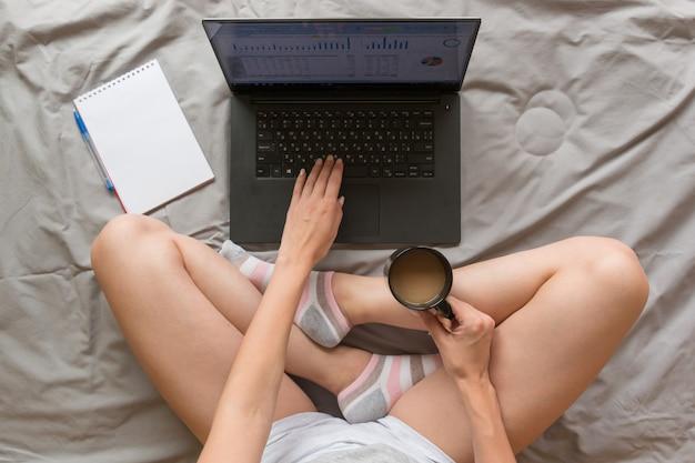 Концепция домашнего офиса: девушка работает с ноутбуком в постели у себя дома