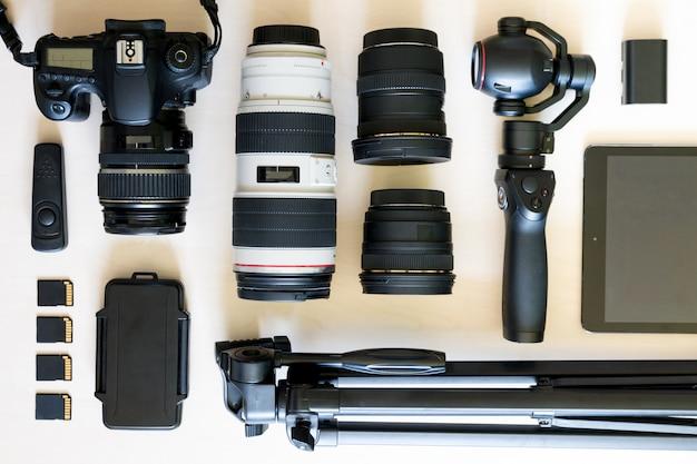 Вид сверху коллекции фототехники с камерой, видеокамерой, объективом и штативом