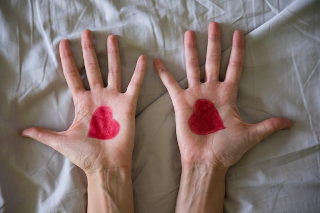 Рисование сердца на руках молодой женщины