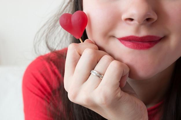 Девушка с конфетой в форме сердца в день святого валентина