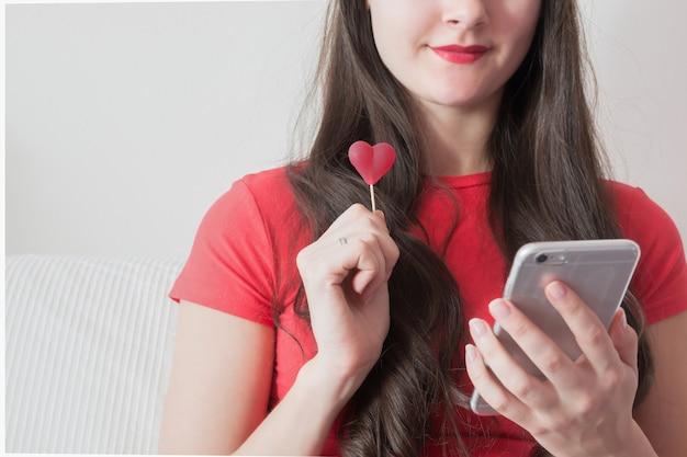 Девушка текстовых сообщений на смартфон с конфетой в день святого валентина