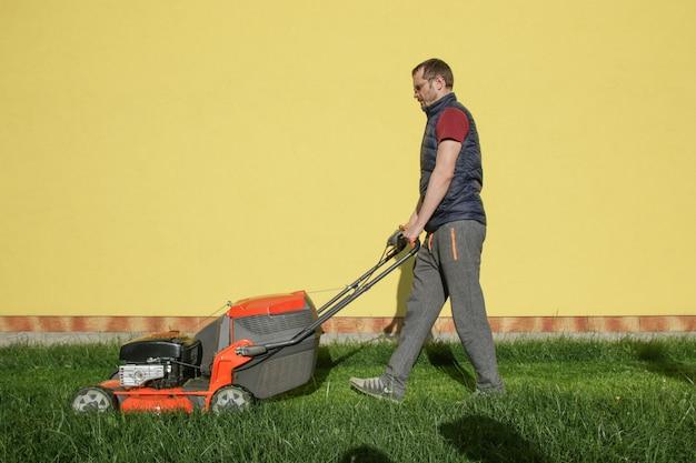 裏庭で芝生を刈る男