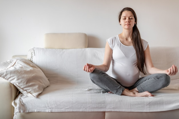 Молодая беременная женщина сидит на белом диване и занимается йогой