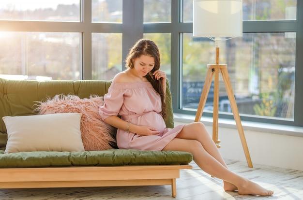 Молодая беременная молодая женщина, наслаждаясь солнечным утром возле большого окна в доме