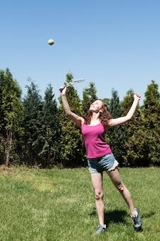ラケットと裏庭にボールを持つ少女