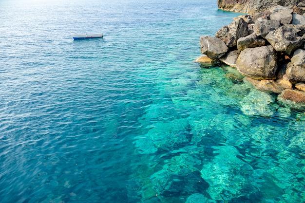 青い澄んだ水と島のサントリーニ島、ギリシャの岩