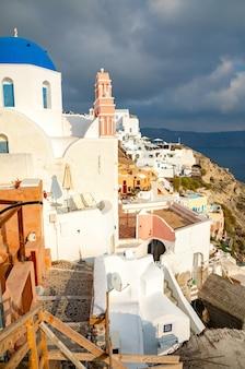 イア、サントリーニ島、ギリシャの伝統的で有名な家と青いドームのある教会