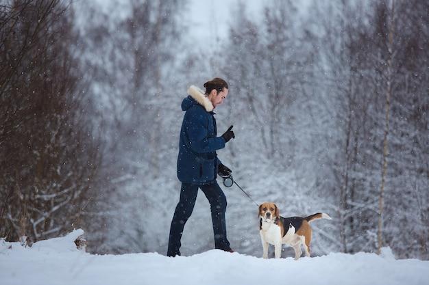 Человек, обучение собака бигль в зимний период. снежный день