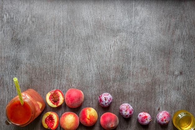 Стакан смузи из персика и сливы на деревянном фоне