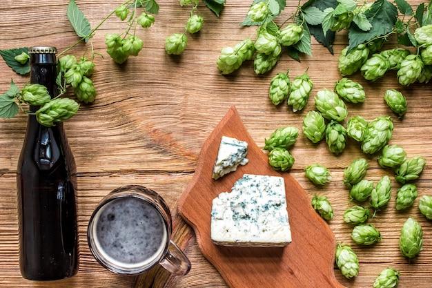 ビールの背景。新鮮なビールと木製のテーブルの塩辛いチーズ。上面図