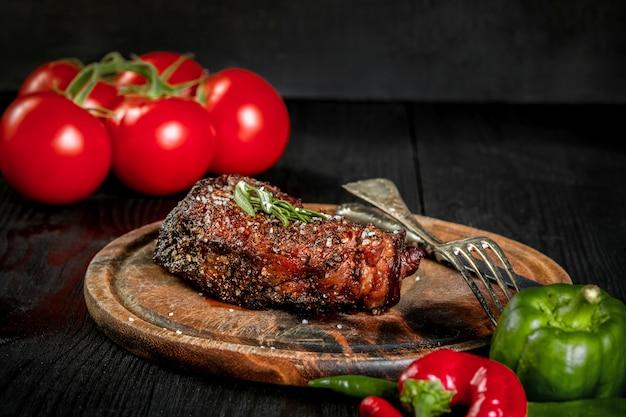Стейк на гриле, приправленный специями и свежей зеленью, подается на деревянной доске со свежими помидорами и красным и зеленым перцем