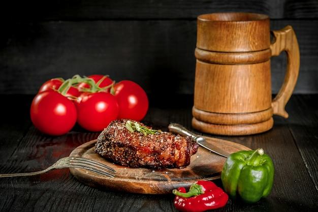 Стейк на гриле, приправленный специями и свежей зеленью, подается на деревянной доске с деревянной кружкой пива, свежими помидорами, красным и зеленым перцем