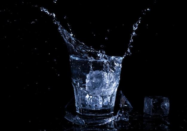 Всплеск воды в стакане. стакан холодной воды. холодная вода со льдом
