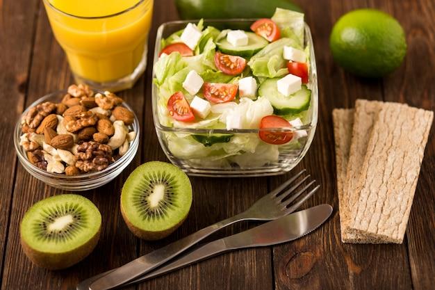 Свежий салат и фрукты на деревянный стол. фитнес завтрак