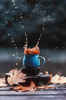 Всплеск кофе на открытом воздухе. осенняя композиция на открытом воздухе. осень. чашка горячего кофе на открытом воздухе.